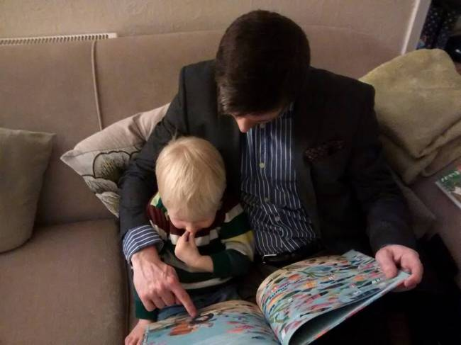 Thomas enjoying reading time with his dad Will