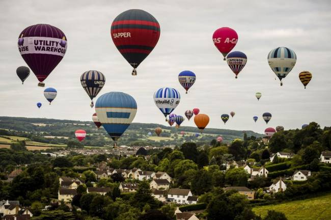 Hot air balloons flying over the Ashton Court Estate towards Long Ashton after taking off in a mass ascent at the Bristol International Balloon Fiesta. Image: Ben Birchall/PA Wire