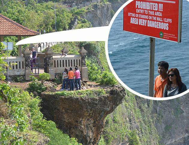 Some very silly tourists at Uluwatu, who don't know they're standing on a ledge | Image: James Draven