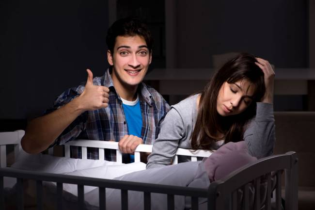 tired parents next to a cot
