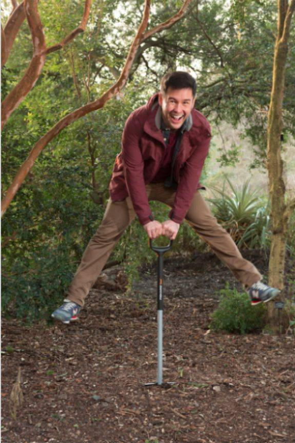 Man holding a spade and doing a star jump